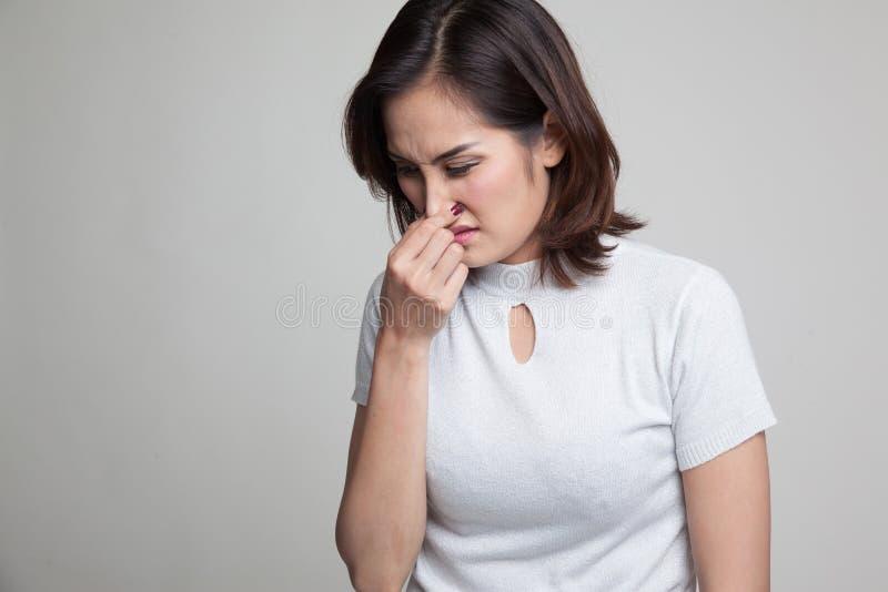 Mulher asiática nova que guarda seu nariz devido a um cheiro mau fotografia de stock