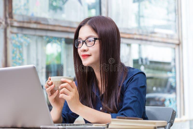 Mulher asiática nova que guarda a xícara de café e que toma uma ruptura de imagem de stock royalty free