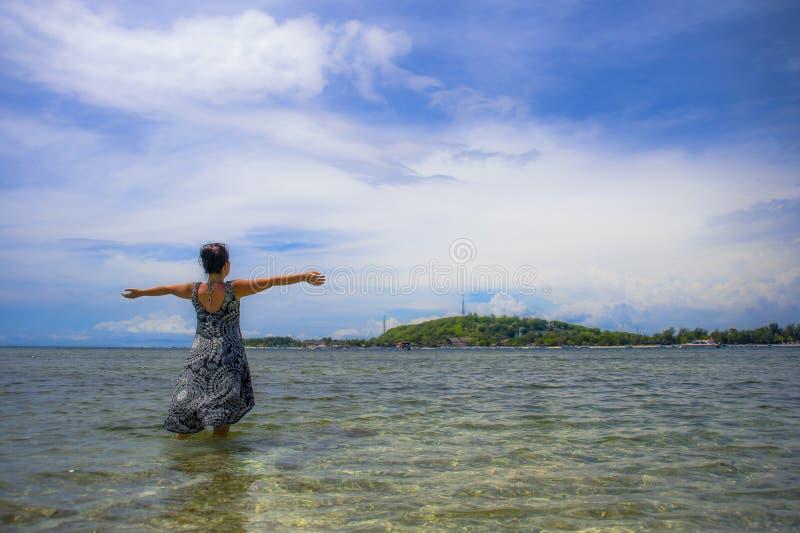 Mulher asiática nova que levanta com os braços abertos na praia em Bali Indon imagens de stock royalty free