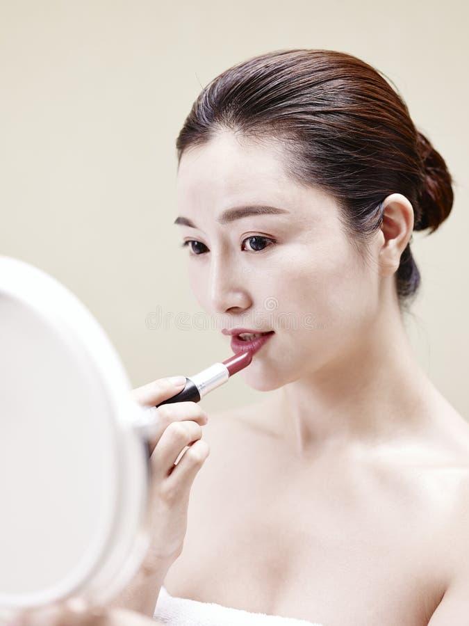 Mulher asiática nova que olha no espelho ao aplicar o batom fotos de stock