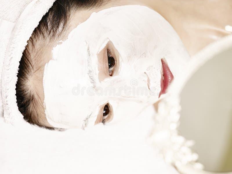 Mulher asiática nova que olha no espelho ao receber t facial imagem de stock royalty free