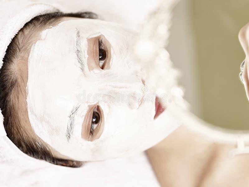 Mulher asiática nova que olha no espelho ao receber t facial foto de stock royalty free