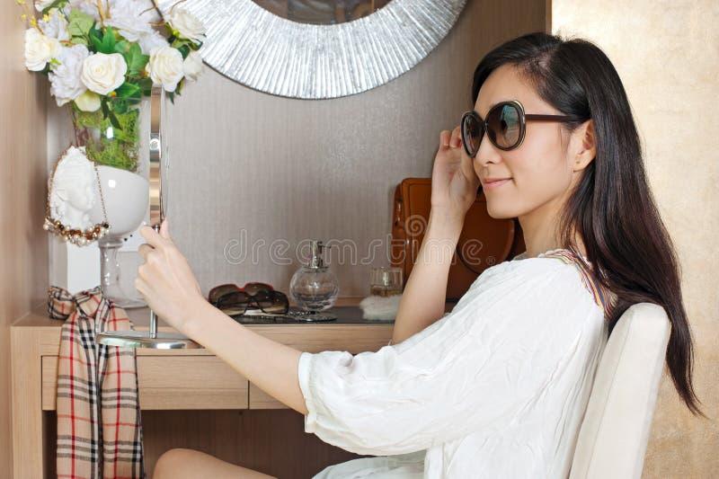 Mulher asiática nova que olha o espelho ao tentar vidros imagens de stock