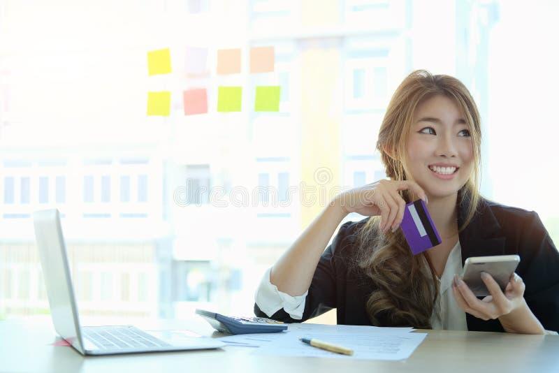 Mulher asiática nova que paga com o cartão de crédito no telefone esperto em casa foto de stock royalty free