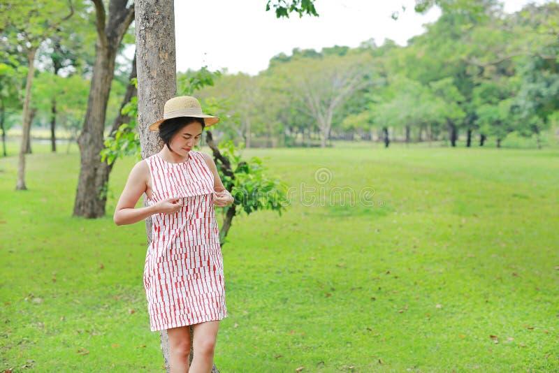Mulher asiática nova que relaxa no jardim do verão fotos de stock