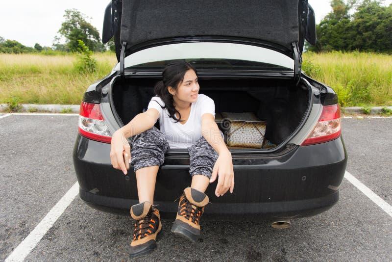 Mulher asiática nova que senta-se no tronco de carro fotografia de stock royalty free