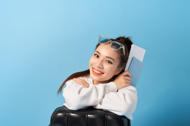 Mulher asiática nova que senta-se perto de um passaporte da terra arrendada da mala de viagem em um fundo azul foto de stock royalty free
