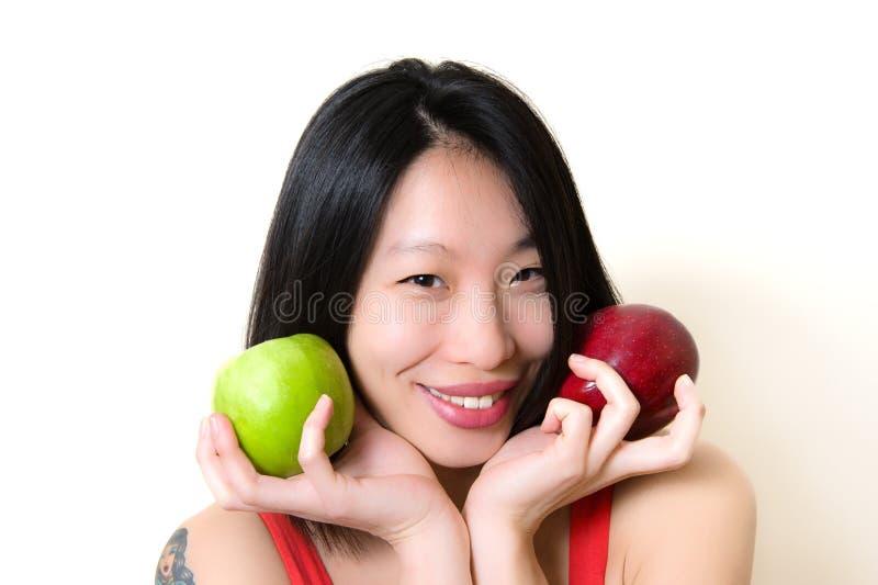 Mulher asiática nova que sorri com as maçãs verdes e vermelhas imagens de stock royalty free
