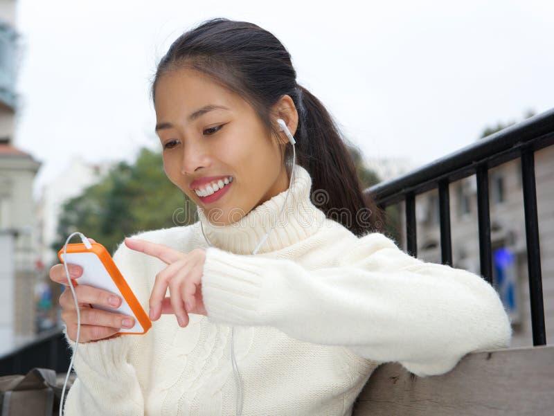 Mulher asiática nova que sorri com telefone celular e fones de ouvido imagens de stock
