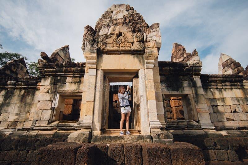 Mulher asiática nova que toma a foto do thom do kok do sdok do prasat em Tailândia fotos de stock