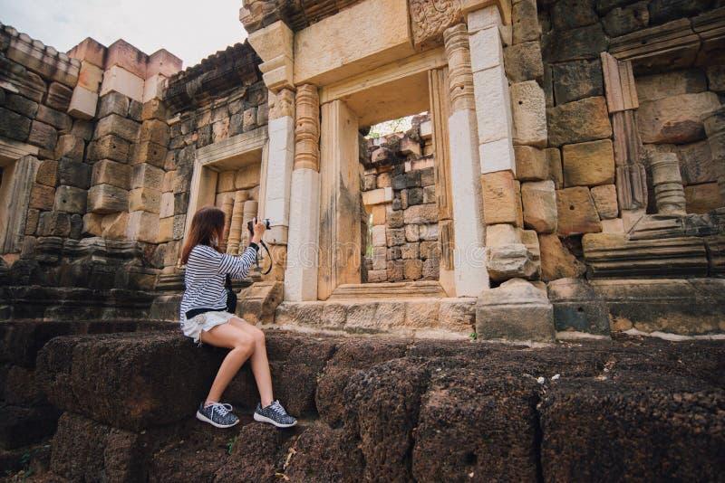 Mulher asiática nova que toma a foto do thom do kok do sdok do prasat em Tailândia com câmera imagem de stock
