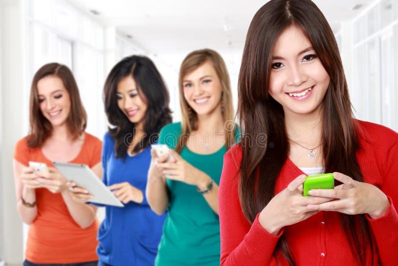 Mulher asiática nova que usa o dispositivo móvel com a mulher diversa no fotografia de stock
