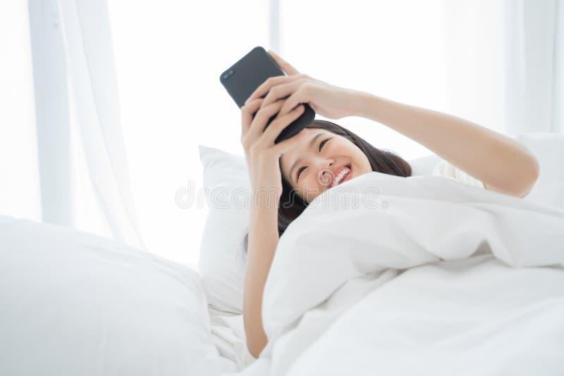 Mulher asiática nova que usa o telefone esperto no quarto feliz e no sorriso imagem de stock