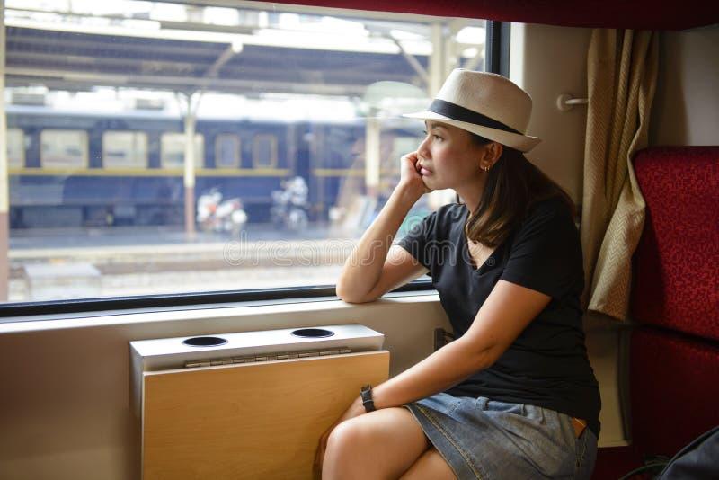 Mulher asiática nova que viaja olhando para fora a janela ao sentar-se no trem imagens de stock