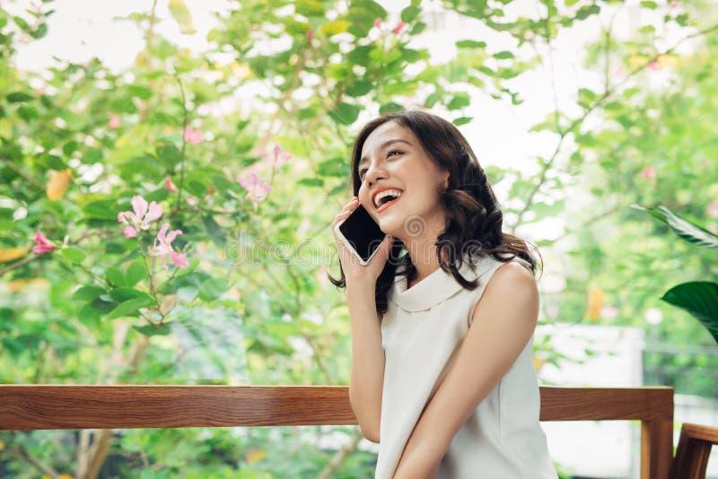 Mulher asiática nova segura no vestuário desportivo esperto que fala ao mobi fotos de stock royalty free