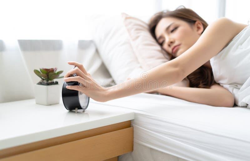 Mulher asiática nova sonolento que tenta o despertador próximo quando cara do enterro no descanso Menina que tem o problema com l foto de stock royalty free