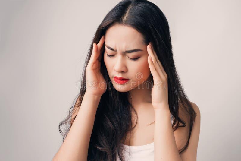 A mulher asiática nova tem a dor de cabeça seriamente foto de stock
