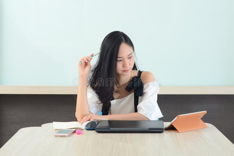 Mulher asiática que analisa o trabalho com portátil e livros no escritório imagens de stock royalty free
