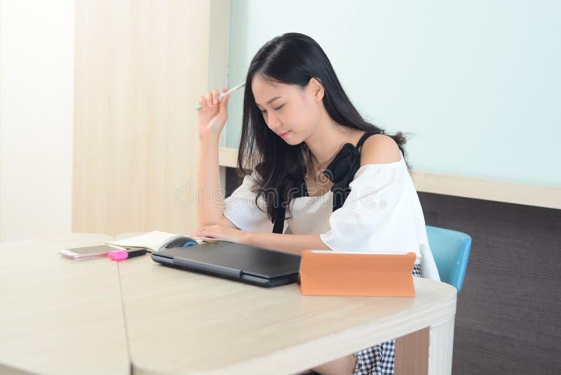 Mulher asiática que analisa o trabalho com portátil e livros no escritório foto de stock