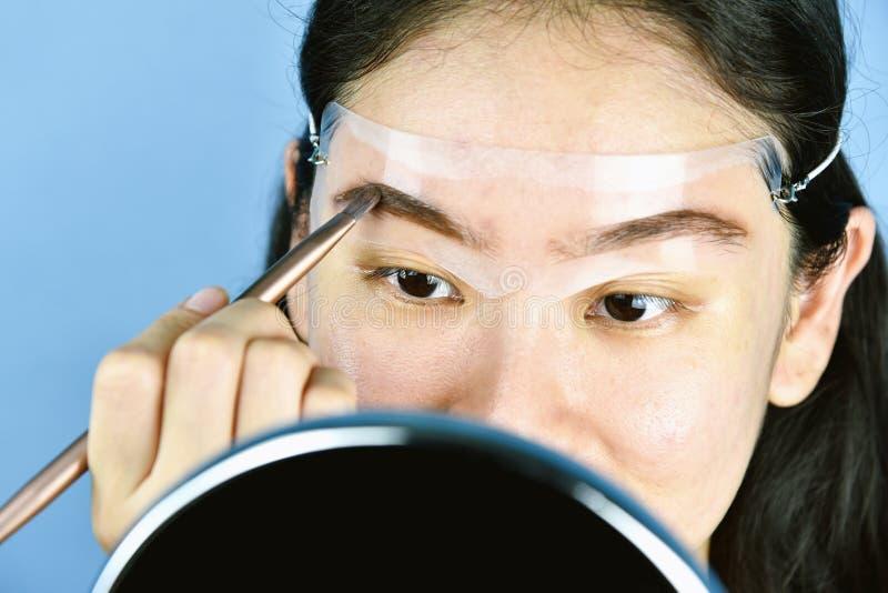 Mulher asiática que aplica a composição dos cosméticos, uso da correia da cabeça do molde das sobrancelhas para dar forma às test foto de stock royalty free
