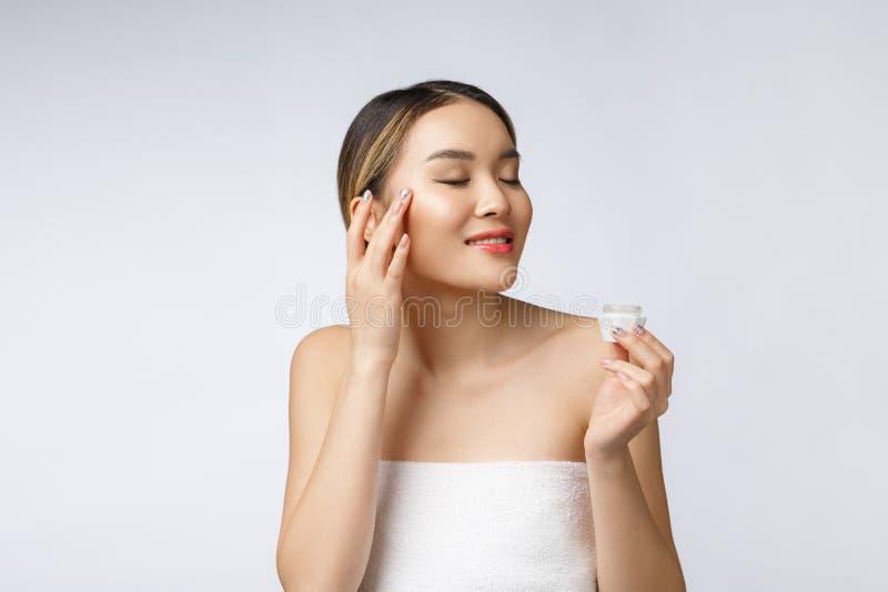 Mulher asiática que aplica o creme cosmético na pele no fundo branco isolado imagem de stock royalty free