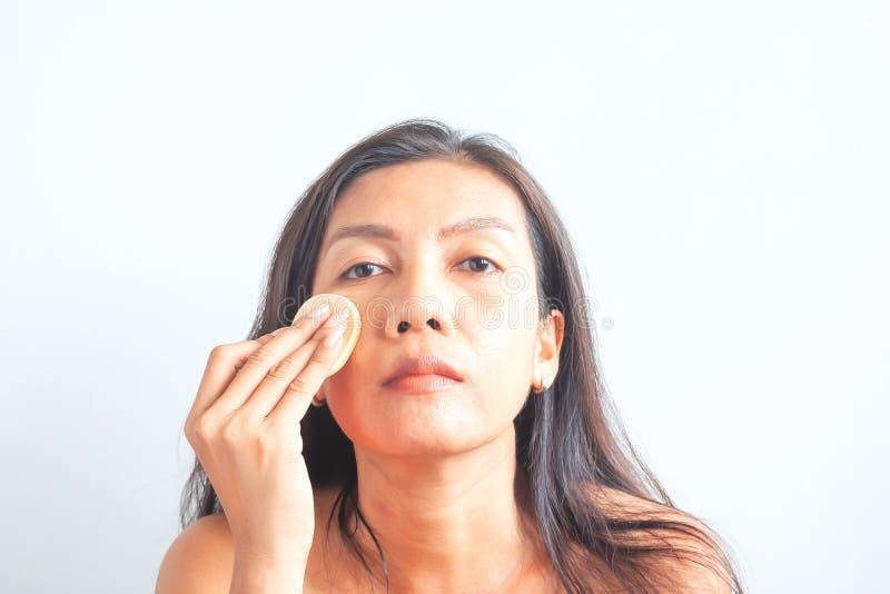 Mulher asiática que aplica o pó da fundação na cara, problema de pele Beleza e sa?de imagens de stock