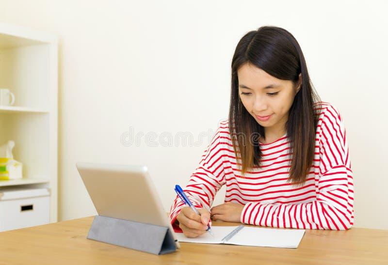 Mulher asiática que aprende através da tabuleta digital foto de stock royalty free