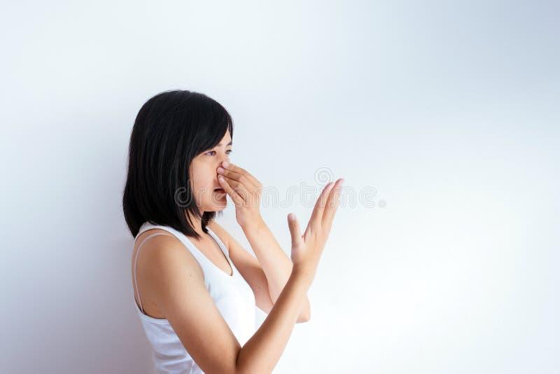 A mulher asiática que cobre seu nariz e cheira sua respiração com upter da mão acorda, cheiro mau foto de stock