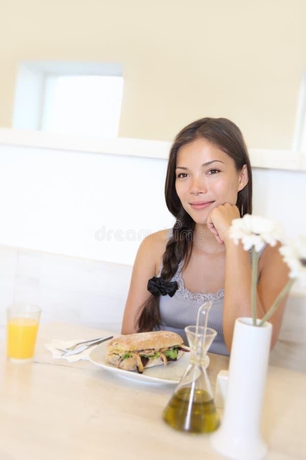 Mulher asiática que come no café foto de stock