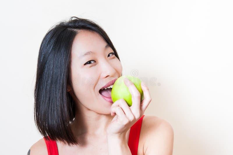 Mulher asiática que come o fundo verde do branco do close up da maçã foto de stock