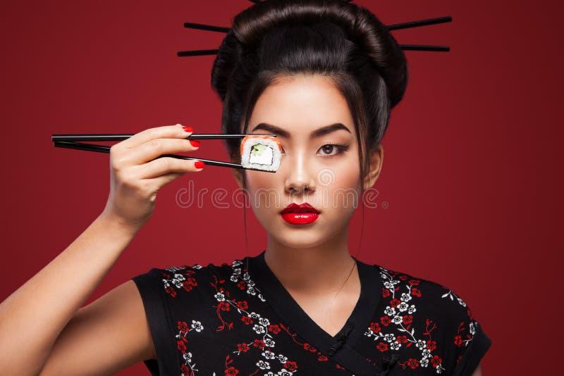 Mulher asiática que come o sushi e os rolos em um fundo vermelho 8 - Oito março, Black Friday, festival japonês de Setsubun, sush fotos de stock