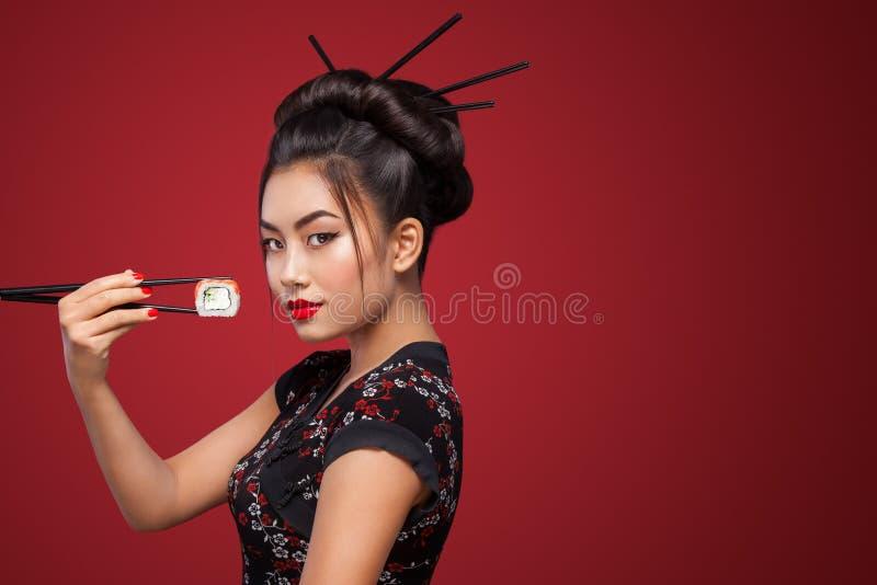 Mulher asiática que come o sushi e os rolos em um fundo vermelho 8 - Oito março, Black Friday, festival japonês de Setsubun, sush fotos de stock royalty free