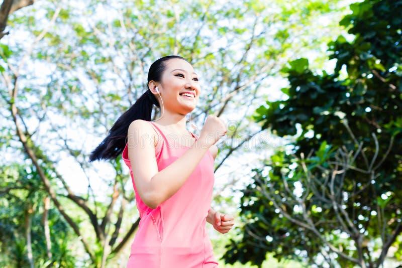 Mulher asiática que corre no parque da cidade fotografia de stock
