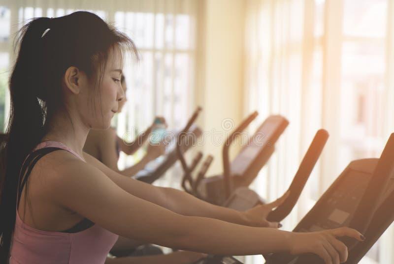 Mulher asiática que dá certo na máquina do gym da aptidão fotos de stock