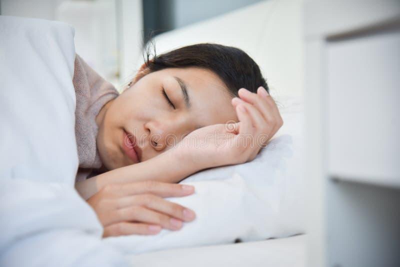 Mulher asiática que dorme em sua cama fotografia de stock