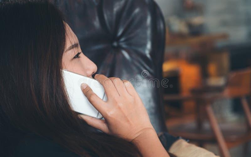 Mulher asiática que encontra-se no sofá preto, usando-se e falando no telefone esperto no café moderno imagem de stock royalty free