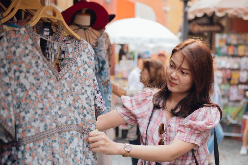 A mulher asiática que escolhe o verão veste-se na loja de roupa no mercado do shopping fotografia de stock royalty free