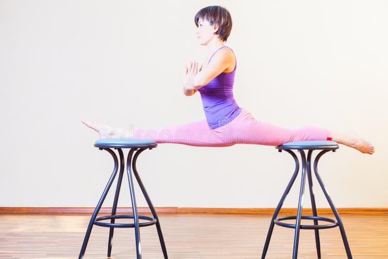 Mulher asiática que estica para o exercício da ioga em casa por cadeiras fotografia de stock royalty free