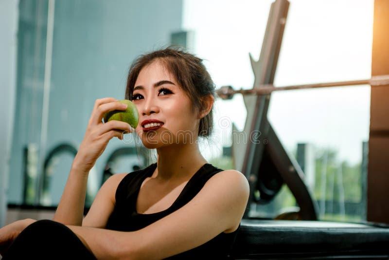 Mulher asiática que exercita no gym imagem de stock