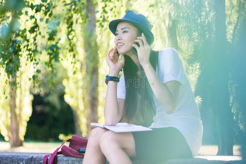 Mulher asiática que fala no telefone celular fora imagens de stock royalty free