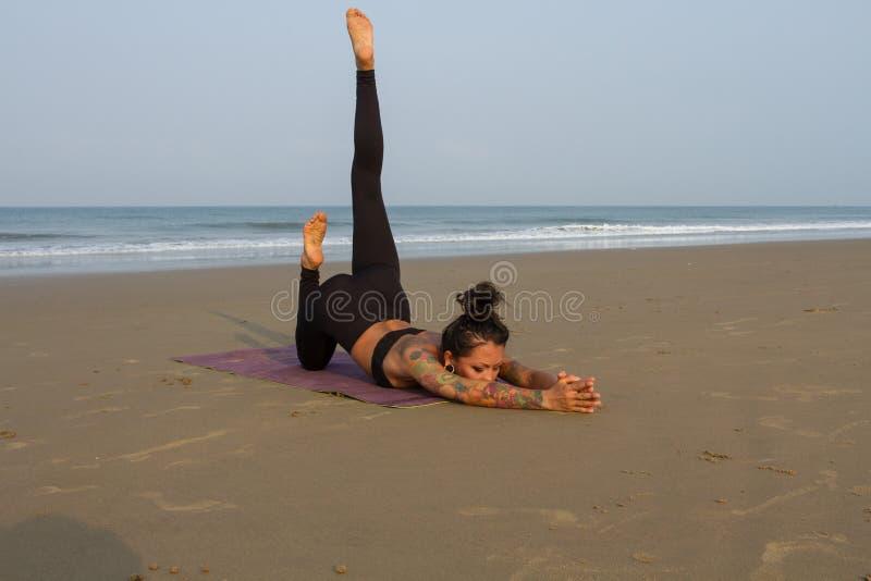 Mulher asiática que faz a ioga nas costas de um mar morno foto de stock