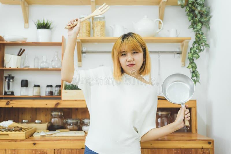 Mulher asiática que faz o alimento saudável que está o sorriso feliz na cozinha que prepara a salada Jovem mulher asiática alegre imagens de stock