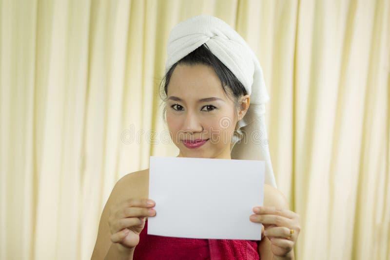 Mulher asiática que guarda a bandeira vazia vazia e a atuação veste uma saia para cobrir seu peito após o cabelo da lavagem,  fotos de stock