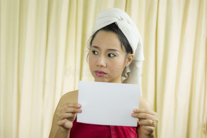 Mulher asiática que guarda a bandeira vazia vazia e a atuação veste uma saia para cobrir seu peito após o cabelo da lavagem,  imagem de stock royalty free