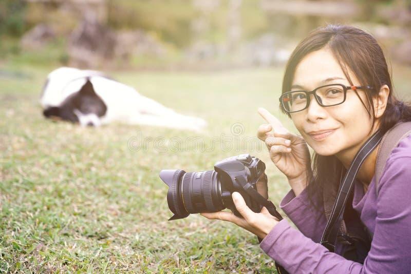Mulher asiática que guarda a câmera e que aponta ao cão fotografia de stock