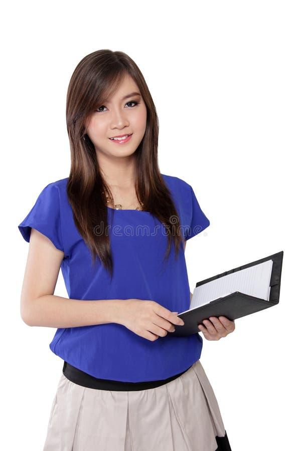 Mulher asiática que guarda o caderno e o sorriso imagem de stock