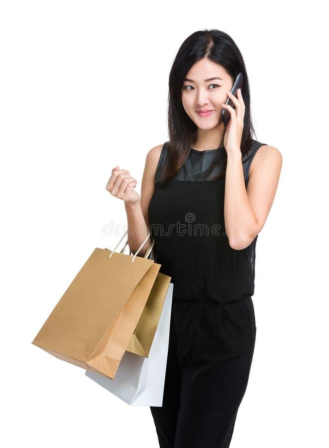 A mulher asiática que guarda o saco shooping e escuta telefone celular fotos de stock
