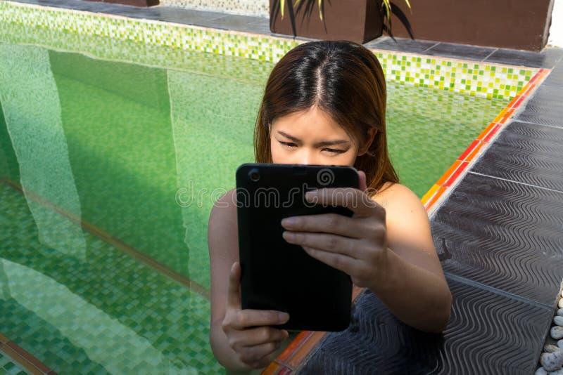 Mulher asiática que guarda a tabuleta na piscina fotografia de stock