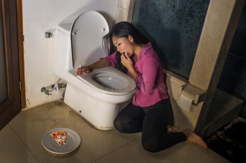 A mulher asiática que joga acima o forçamento com os dedos para vomitar o sentimento da pizza culpado preocupou-se sobre a obtenç foto de stock