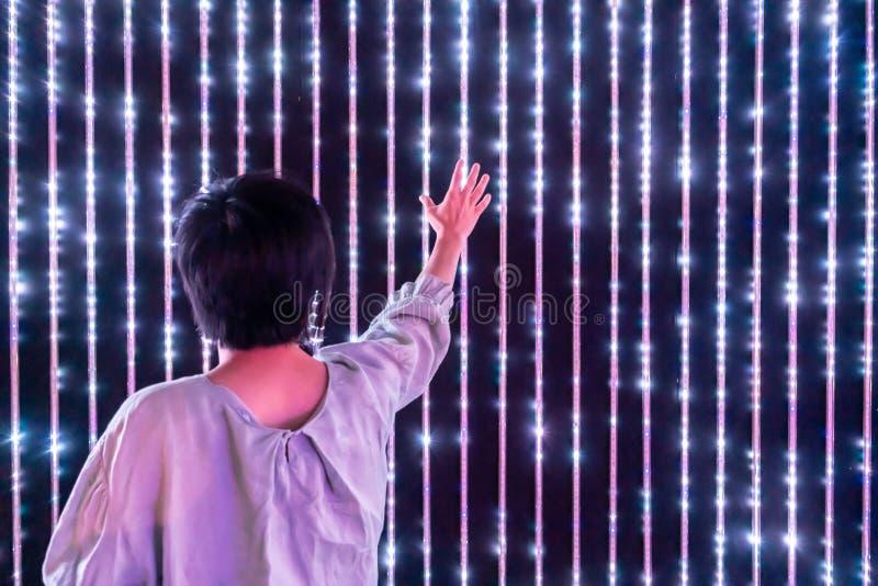Mulher asiática que joga com a parede leve conduzida da interação foto de stock royalty free